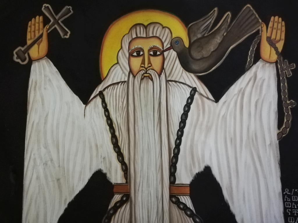 Kuvassa enkelihahmo, jolla toisessa kädessä risti, toisessa rukoushelmet ja kyyhkynen laskeutumassa olkapäälle.