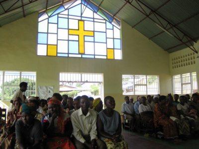 HIV/Aids -projektilaisia ruandalaisessa kirkossa, jonka seinässä ristinmuotoinen, valoissa lasiteos.