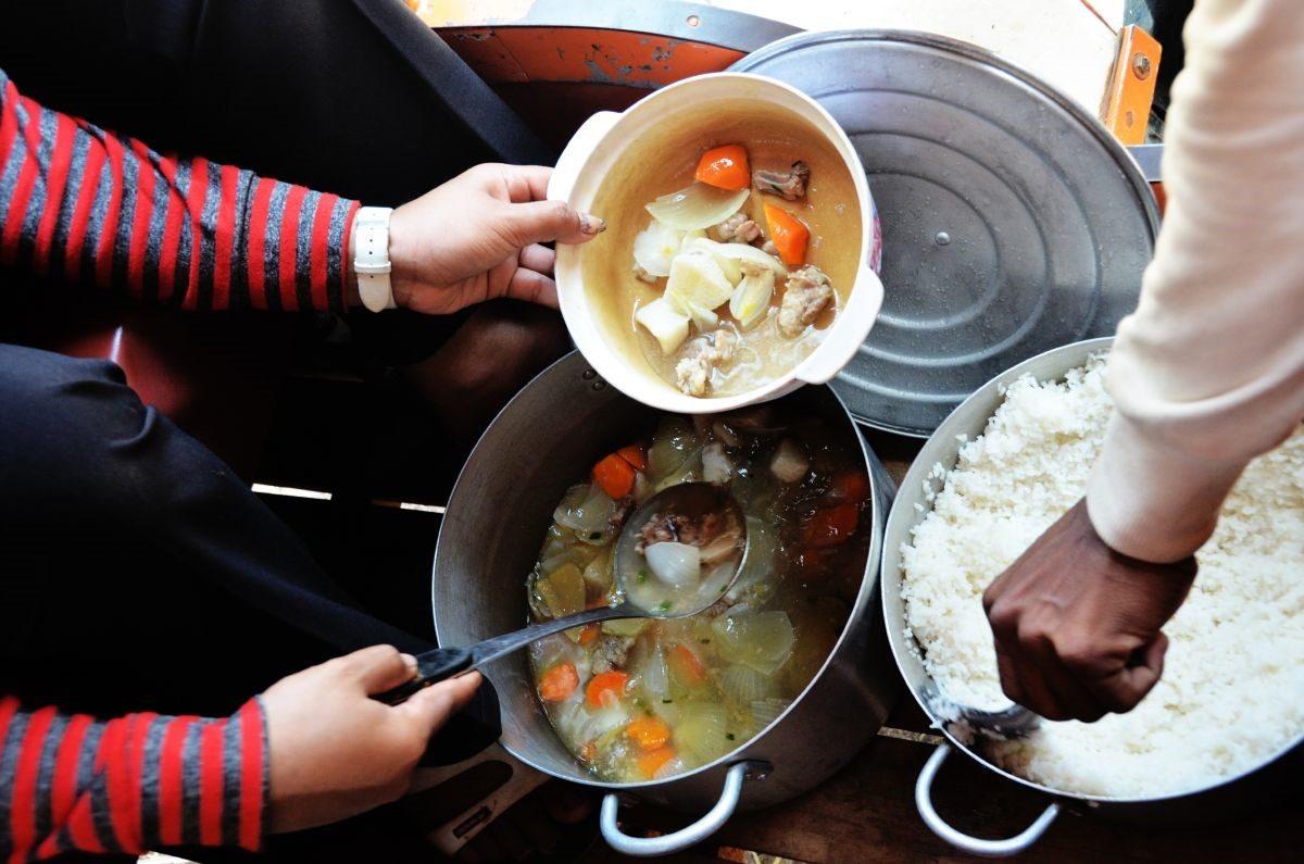 Ruoanjakamista: kädet, jotka laittavat riisiä ja vihanneskastiketta lautaselle