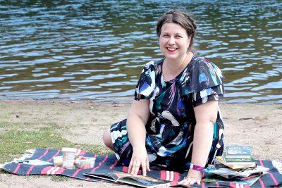 Saara Tiuraniemi istuu viltillä järven rannassa ympärillään kirjoja.
