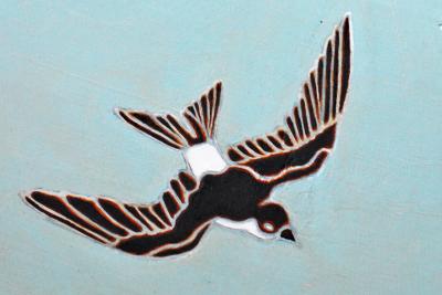 Yksittäinen lintu Osmo Rauhalan alttaripöytään maalaamasta pääskyparvesta. Tyrvään Pyhän Olavin kirkko.