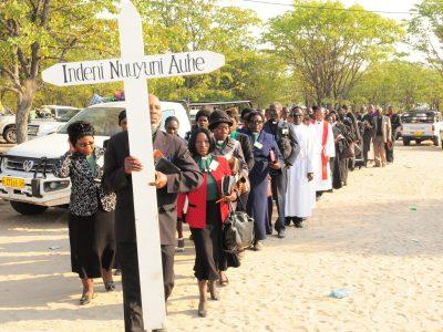 Kuvassa kulkue Namibian luterilaisen kirkon lähtisen hiippakunnan lähetysjuhlilta 2019. Kulkueen kärjessä kyltti, jossa teksti: Indeni nuuyuni auhe, joka tarkoittaa menkää kaikkeen maailmaan.