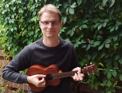 Timo-Matti Haapainen, kirkkohallituksen uskontojen kohtaamisen asiantuntija ukulele kädessään kotipihalla.