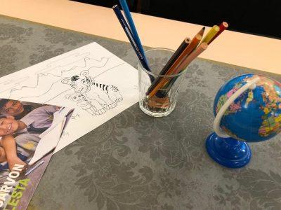 Kuvassa kansainvälisyyskasvatukseen liittyviä välineitä kirjoituspöydällä: kyniä värityskuva, pieni maapallo.
