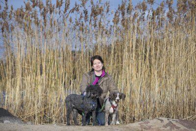 Liisa Kuparinen rantakaislikossa koiransa kanssa.
