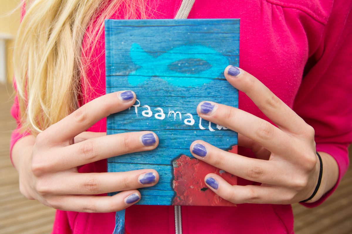 Nuoren naisen kädessä Raamattu
