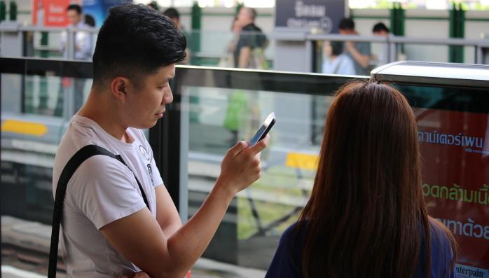 Mobiilin käyttöä juna-asemalla Aasiassa.