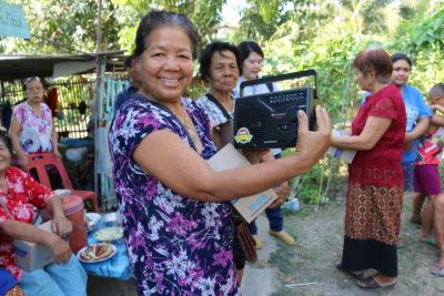 Iloisesti hymyilevä nainen näyttää kädessään olevaa radiota, jonka on juuri saanut lahjoituksena. Sen avulla on mahdollista kuunnella kristillistä opetusta.