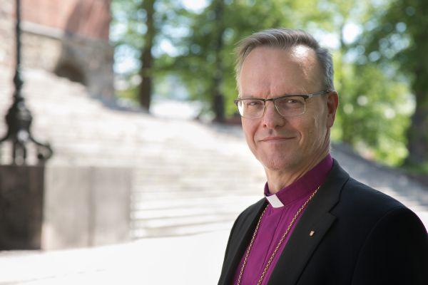 Arkkipiispa Tapio Luoma katsoo kameraan kesäisenä päivänä.