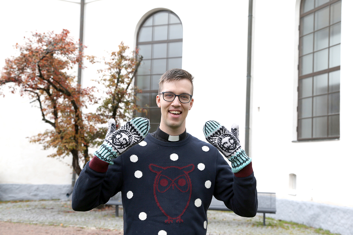 Pastori Ville Halkoluoto Hämeenlinnan kirkon edustalla. Villellä on käsissään Jeesus-kuvioiset lapaset.
