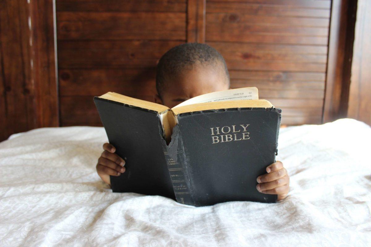 Kuvassa pieni lapsi lukee raamattua.