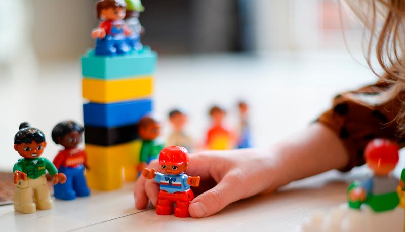 Kuvassa lapsen käsi jossa värikäs muovinen leluhahmo. Kuvassa lisäksi vielä yhdeksän muuta leluhahmoa sekä muutama värikäs leikkirakennuspalikka.