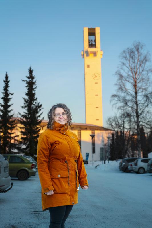 Talvisessa kuvassa on hymyilevä Heli Lavila päällään oranssi toppatakki, taustalla lunta,  Lakeuden Risti -kirkko ja kirkkotorni.