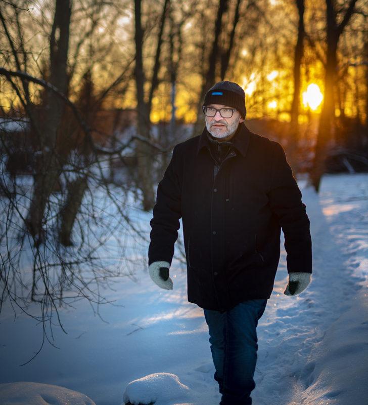Kuvassa Olavi Helpomäki. Olavi astelee talvisessa maisemassa. Taustalla lunta ja lehdettömiä puita.