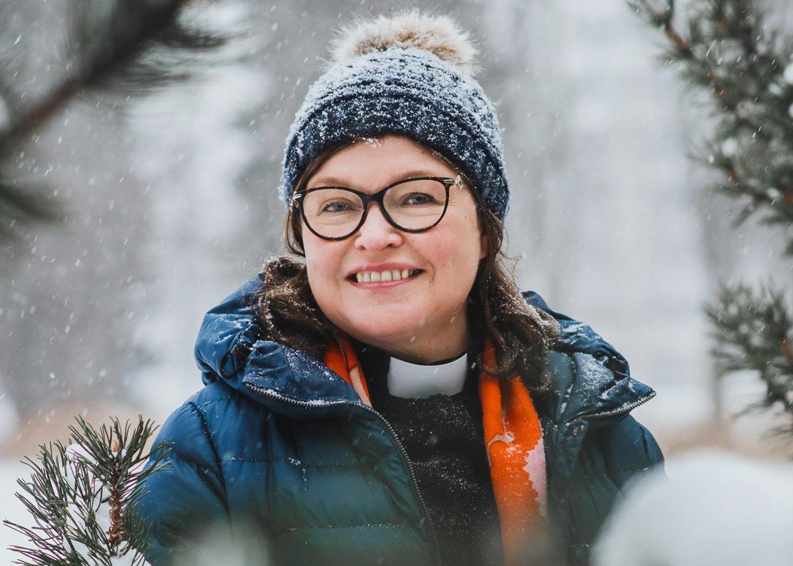 Tarja Autio hymyilee kameralle ulkona otetussa kuvassa. Ulkona sataa lunta ja Tarjalla on päässään sininen pipo jossa karvainen tupsu. Lumisia männyn oksia näkyy kuvan reunoilla.