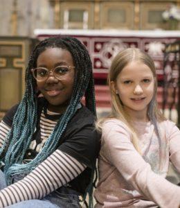 Kaksi lapsikuoron tyttöä Kuusankosken kirkossa.