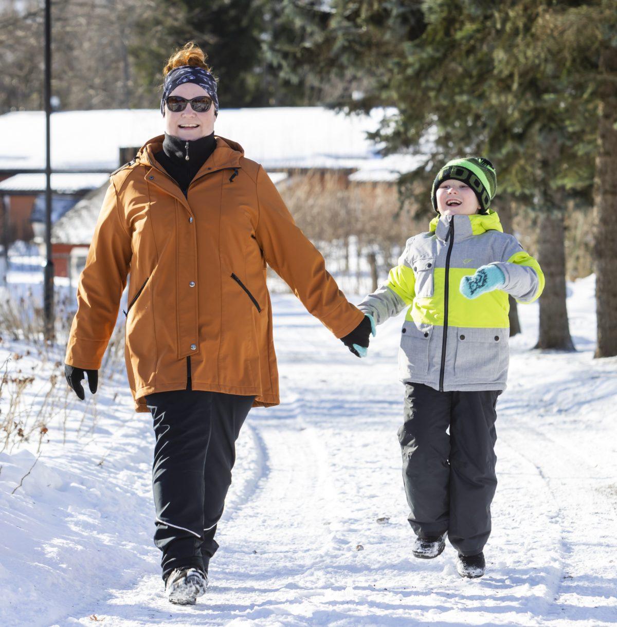 Äiti ja poika iloisina kävelyllä käsi kädessä.