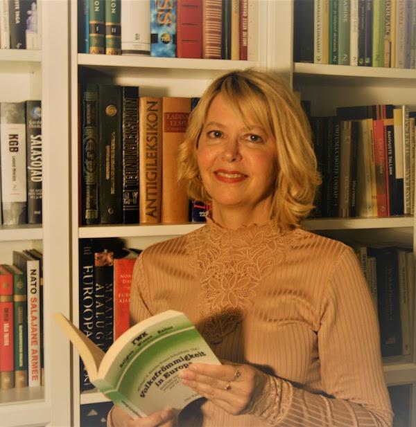 Sosiologi Liina Kilemit kirja kädessään.