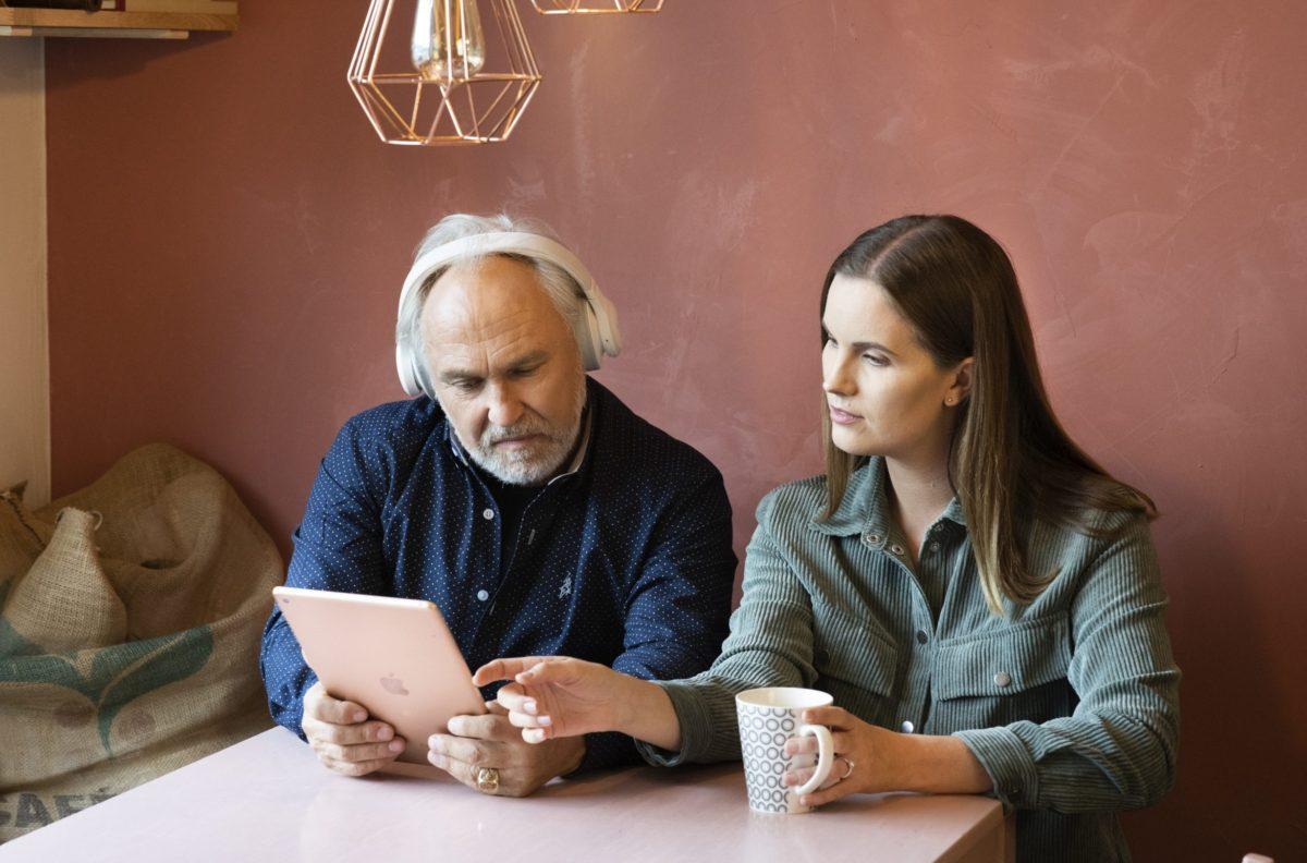 Vanhempi mies ja nuori nainen tutkivat tabletilla Raamattua.