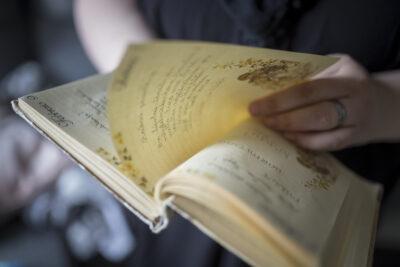 Päiväkirja ja sitä lehteilevät kädet.