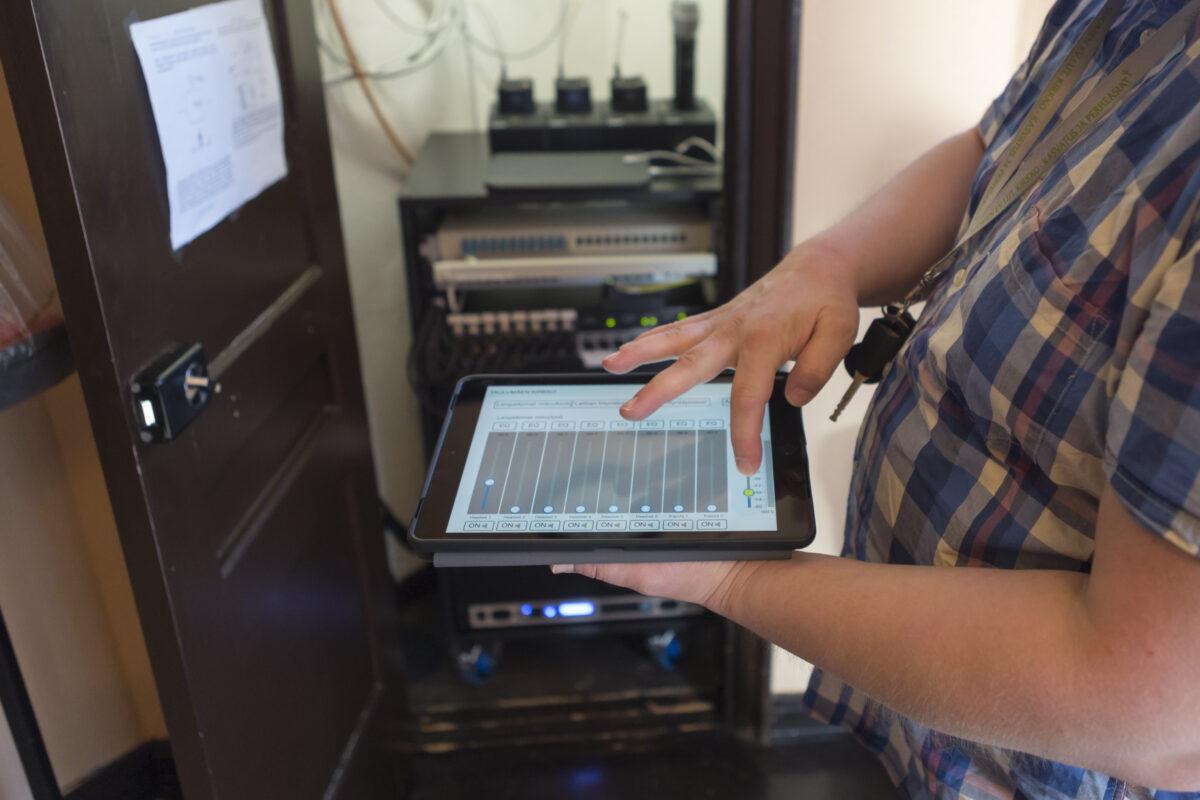 Suntio Miika Salminen kädessään tablettitietokone. Taustalla äänentoistolaitteistoa.