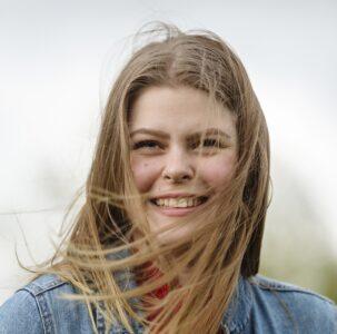 Nuori nainen hymyilee, tuuli tuivertaa hiuksia.