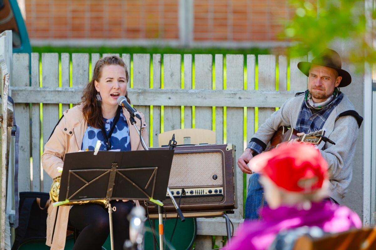Kaksi muusikkoa, mies soittaa kitaraa, nainen laulaa.