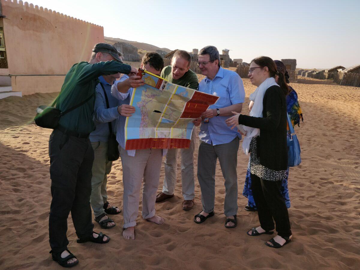 Uskontojen kohtaamisen toimikunnan jäseniä kumartuneena kartan ylle Omanissa
