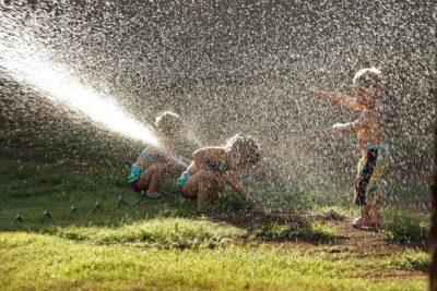 Lapset leikkivät vesisuihkun alla kuumana kesäpäivänä