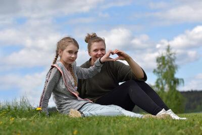 Kummitytär Lilli ja kummi Jenni istuvat nurmella ja tekevät sormillaan sydämen muodon.