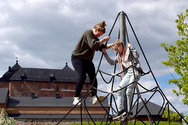 Jenni ja Lilli kiipeilytelineessä. Taustalla näkyy Hämeen linna.