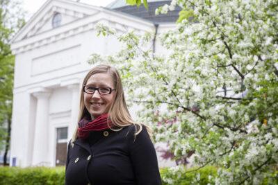Haastateltava keväisen kukkivan puun edessä Hämeenlinnan kirkon luona.