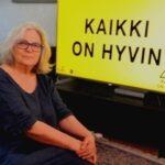 """Tamperelainen Annukka Häkämies ja kyltti, jossa on Evankeliumijuhlien tämän vuoden teema """"Kaikki on hyvin""""."""