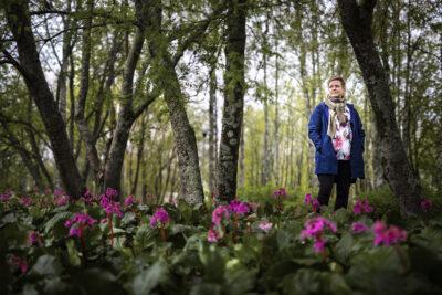 Kuvassa Katja Peltokoski puiden ja kukkien keskellä.
