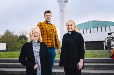 Kuvassa kolme pappia seisomassa portailla Lakeuden Risti -kirkon edustalla.