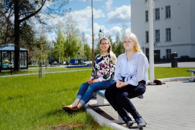 Kuvassa Anu Mäki-Latvala ja Miia Nortunen kesäisen nurmikon reunalla istumassa puiston penkillä.