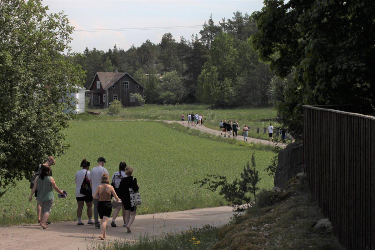 Rippikoululaisia kulkemassa tietä pitkin peltojen halki