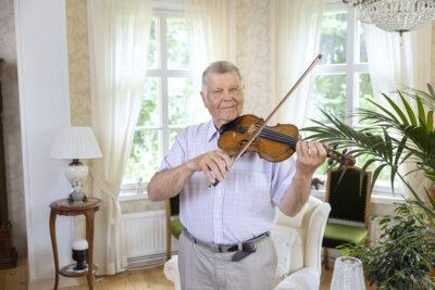 Erkki Hietavirta soittaa viulua olohuoneessaan.
