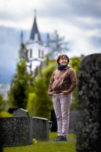Kuvassa Anitta Punkari Ylistaron hautausmaalla, taustalla näkyy Ylistaron kirkko.