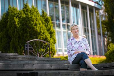 Kuvassa Seija Saari istuu portailla.